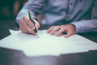 Unas manos sosteniendo un bolígrafo y escribiendo sobre varios folios. Periodo de prueba.