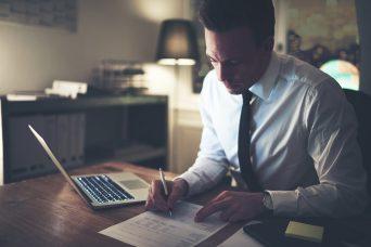 Chico escribiendo sobre un papel y trabajando en la reclamacion de cantidad laboral