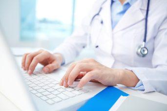 un doctor tecleando en un ordenador para dar la baja laboral a un paciente.
