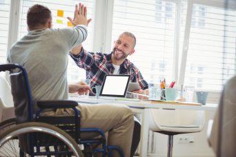 Dos chicos chocando las manos con incapacidad y discapacidad.