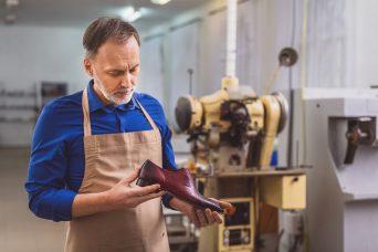 Un hombre trabajando con un zapato en la mano antes de pedir la jubilación anticipada.