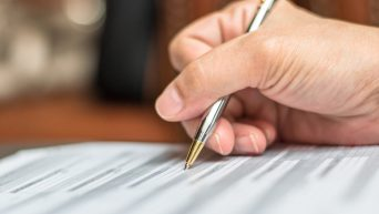 Una mano cogiendo un bolígrafo y firmando unos papeles.