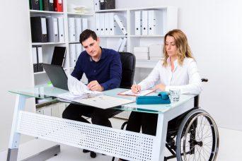 un chico y una chica en silla de ruedas solicitando la Incapacidad Permanente.