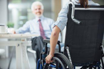 Un hombre sentado de frente y de espaldas una persona sentada en una silla de ruedas que sufre Incapacidad Permanente