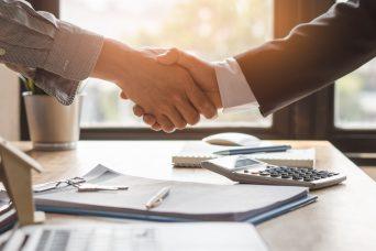 Dos personas dándose la mano después de firmar y hablar acerca de los contratos indefinidos.