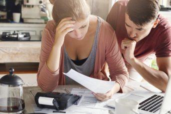 Una pareja revisando documentos para comprobar cómo reclamar salarios atrasados.