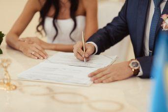 Una pareja recién casada firmando los papeles.