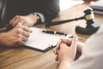 Las manos de dos personas, un formulario y un mazo sobre una mesa